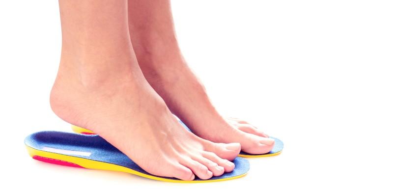 Semelle bleu, jaune et rose sous les pieds d'une personne